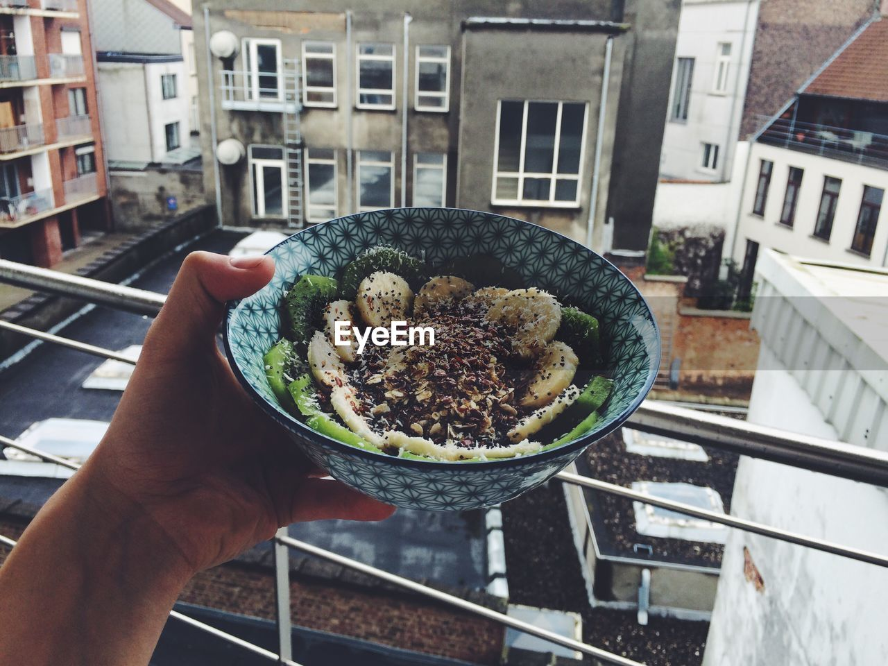 Cropped Hand Holding Breakfast In Bowl At Balcony