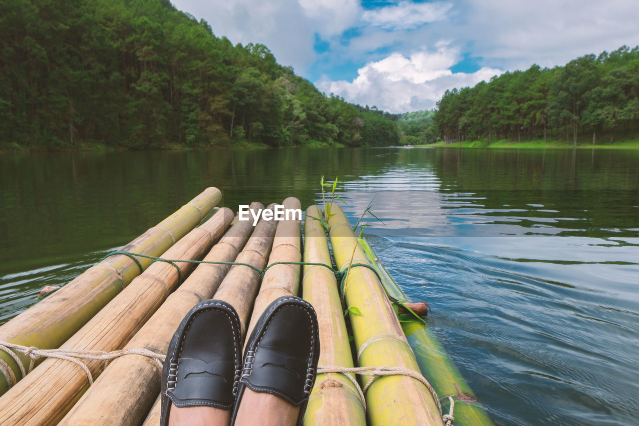 Low section of person on wooden raft in lake against sky