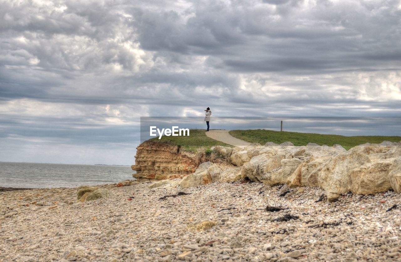 Scenic View Of Landscape By Sea Against Dramatic Sky