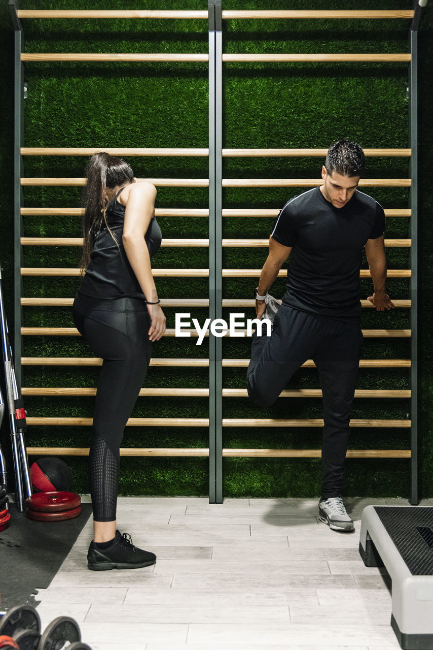 REAR VIEW OF COUPLE STANDING ON FLOOR