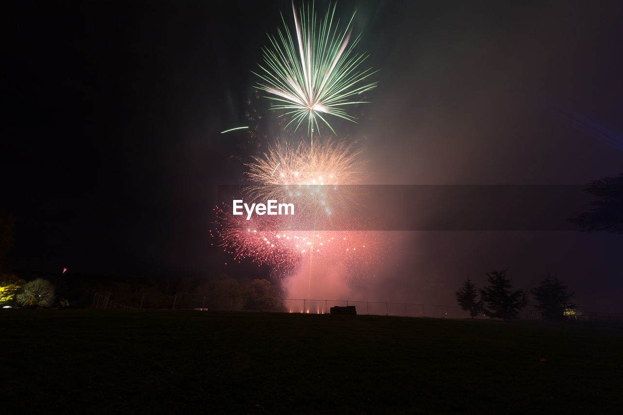 Fireworks explode in the sky with green and red colours through the smokey haze.