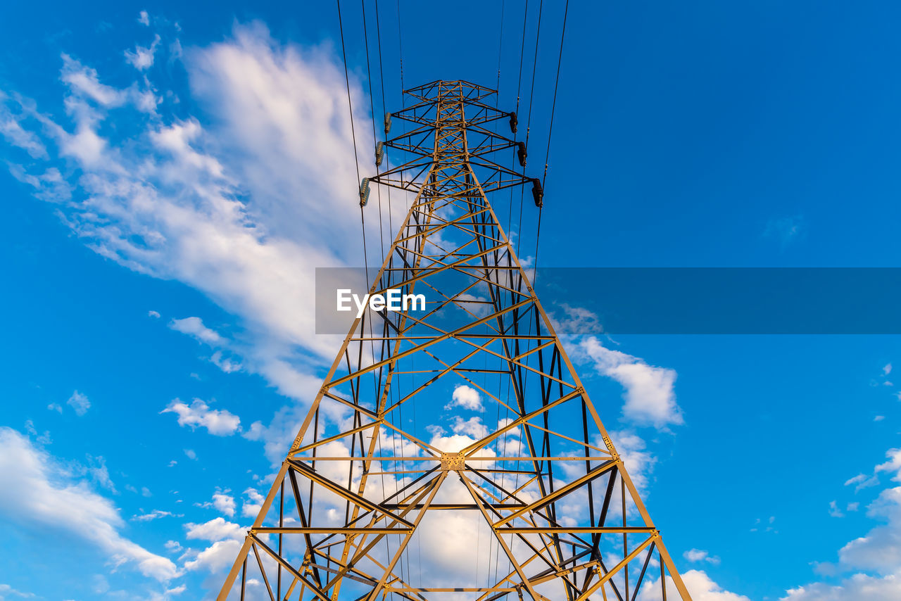 High voltage tower with electricity transmission power lines in sunset light.