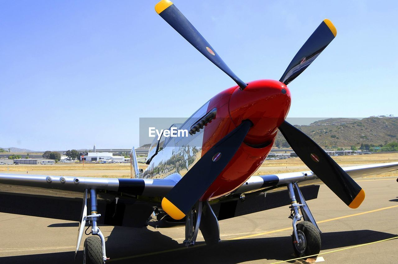 air vehicle, airplane, transportation, day, clear sky, mode of transport, propeller airplane, airport runway, outdoors, no people, airport, aircraft wing, stationary, runway, military airplane, sky, model airplane, flying, airshow, fighter plane, air force, close-up