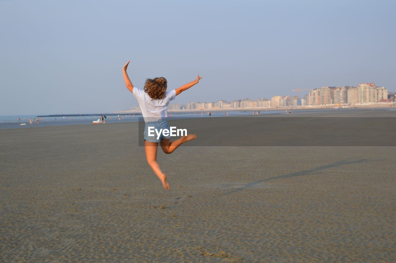 beach, one person, land, sea, full length, sky, human arm, rear view, sand, leisure activity, arms raised, real people, lifestyles, water, limb, jumping, nature, clear sky, freedom, outdoors, positive emotion