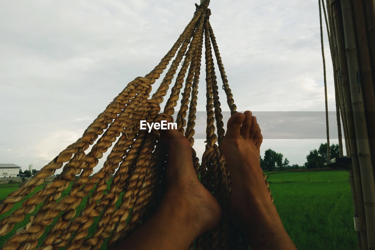human body part, body part, real people, one person, personal perspective, sky, cloud - sky, nature, day, barefoot, human leg, lifestyles, low section, human foot, human hand, hammock, leisure activity, outdoors, built structure, hand, human limb, finger