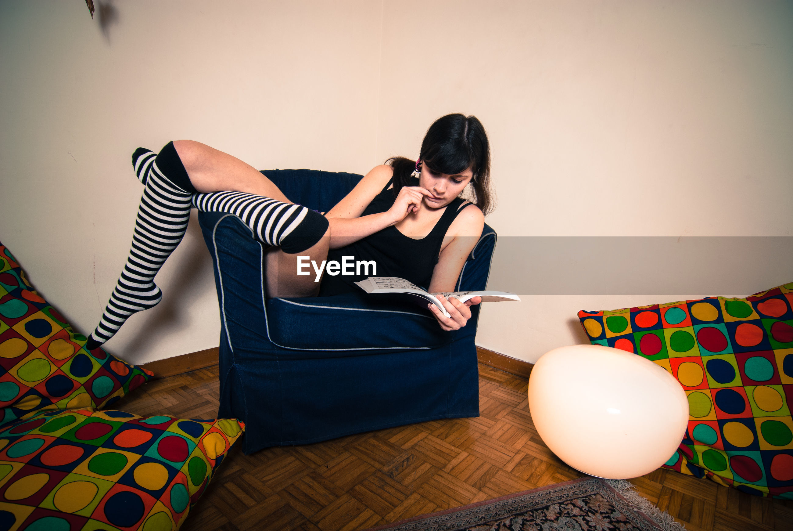 Young woman reading book while relaxing on chair at home