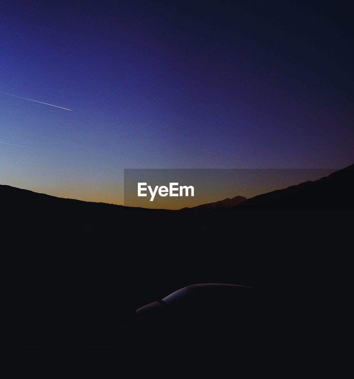 Silhouette mountain against blue sky at dusk