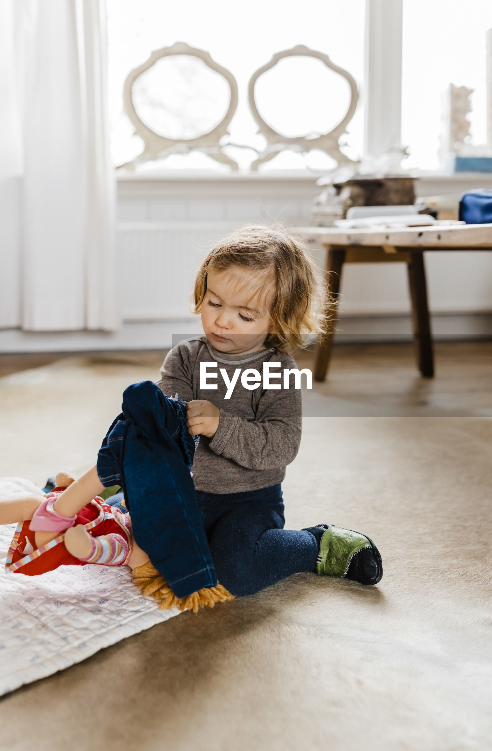 Cute girl wearing jacket while kneeling on floor at home