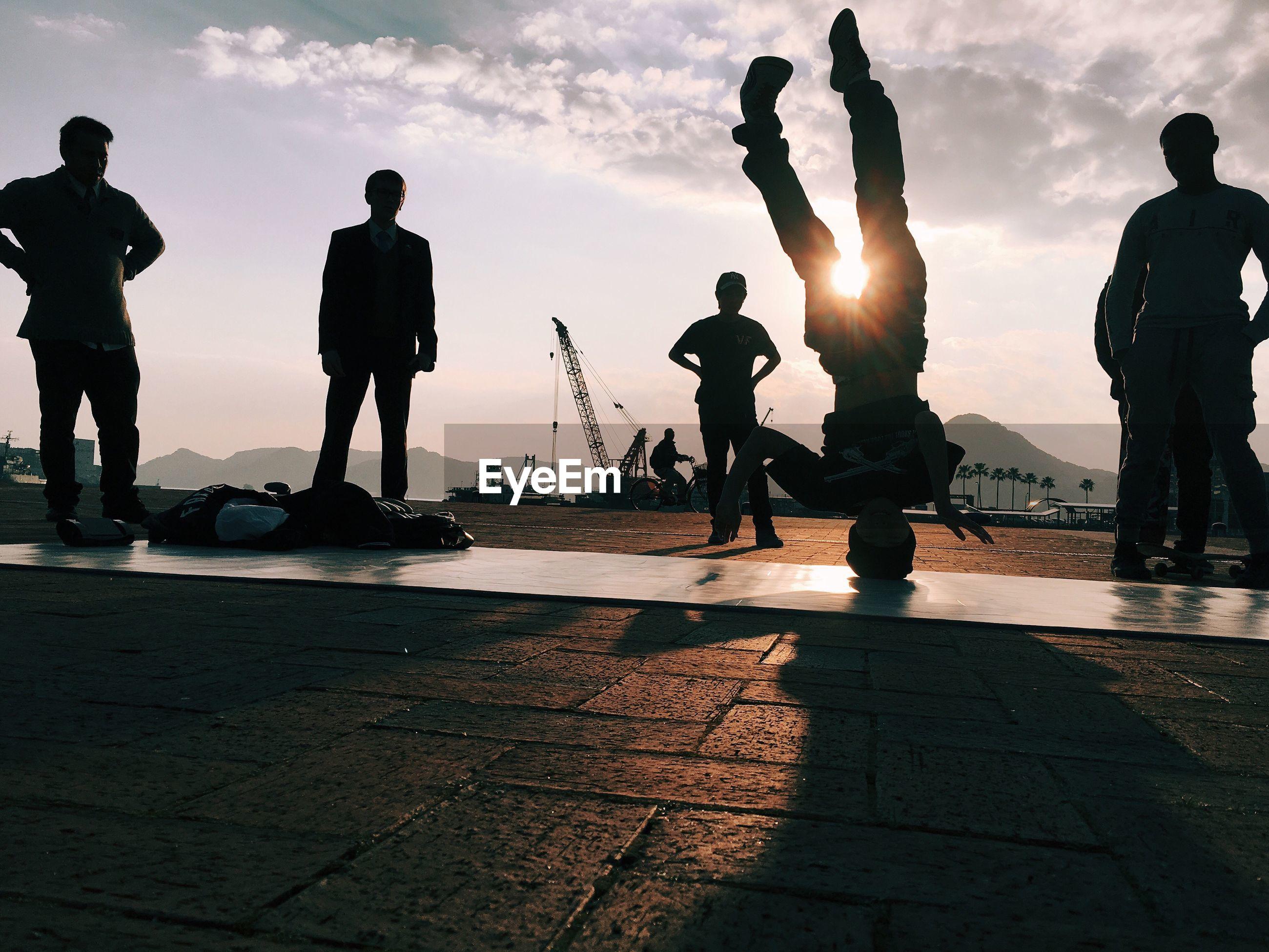 Silhouette people watching man dancing hip hop on pier against sky
