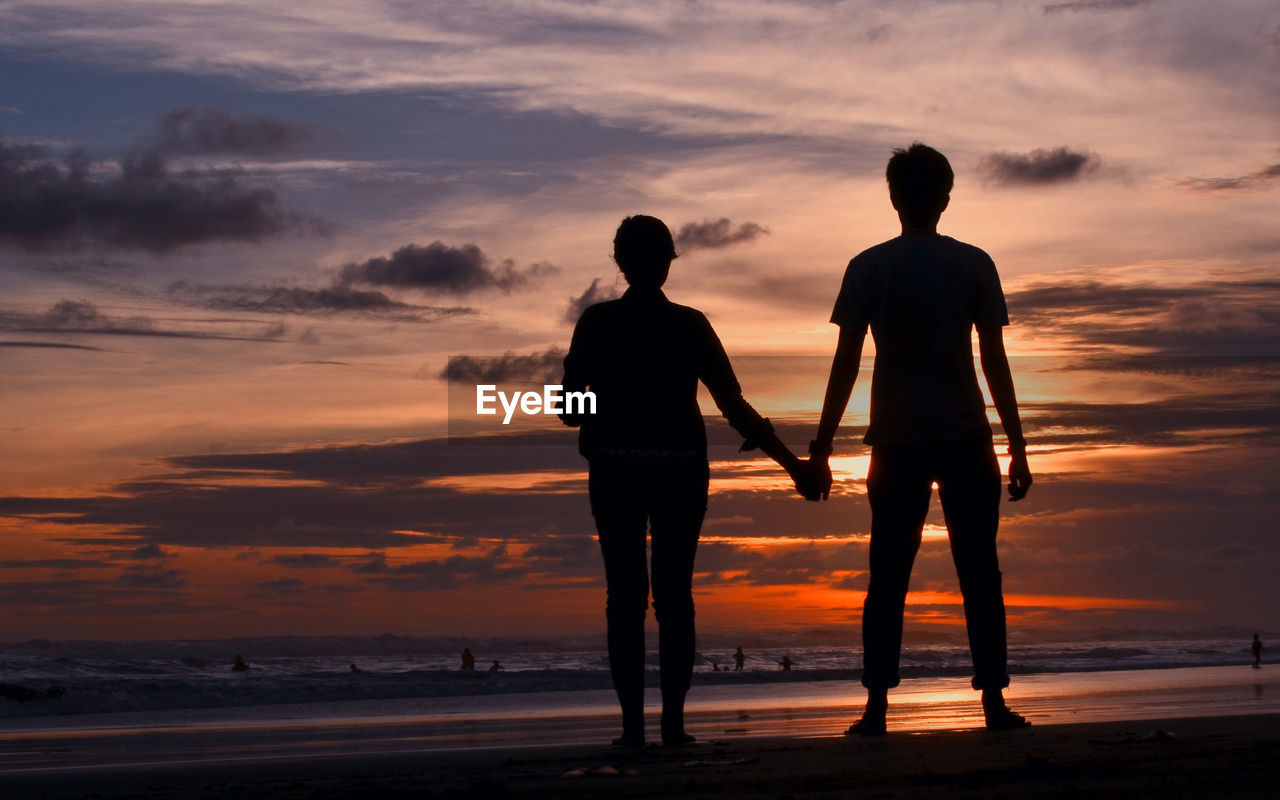 sunset, sky, cloud - sky, silhouette, orange color, togetherness, two people, beauty in nature, land, standing, beach, real people, men, sea, women, full length, bonding, leisure activity, lifestyles, water, positive emotion, outdoors, couple - relationship, sister