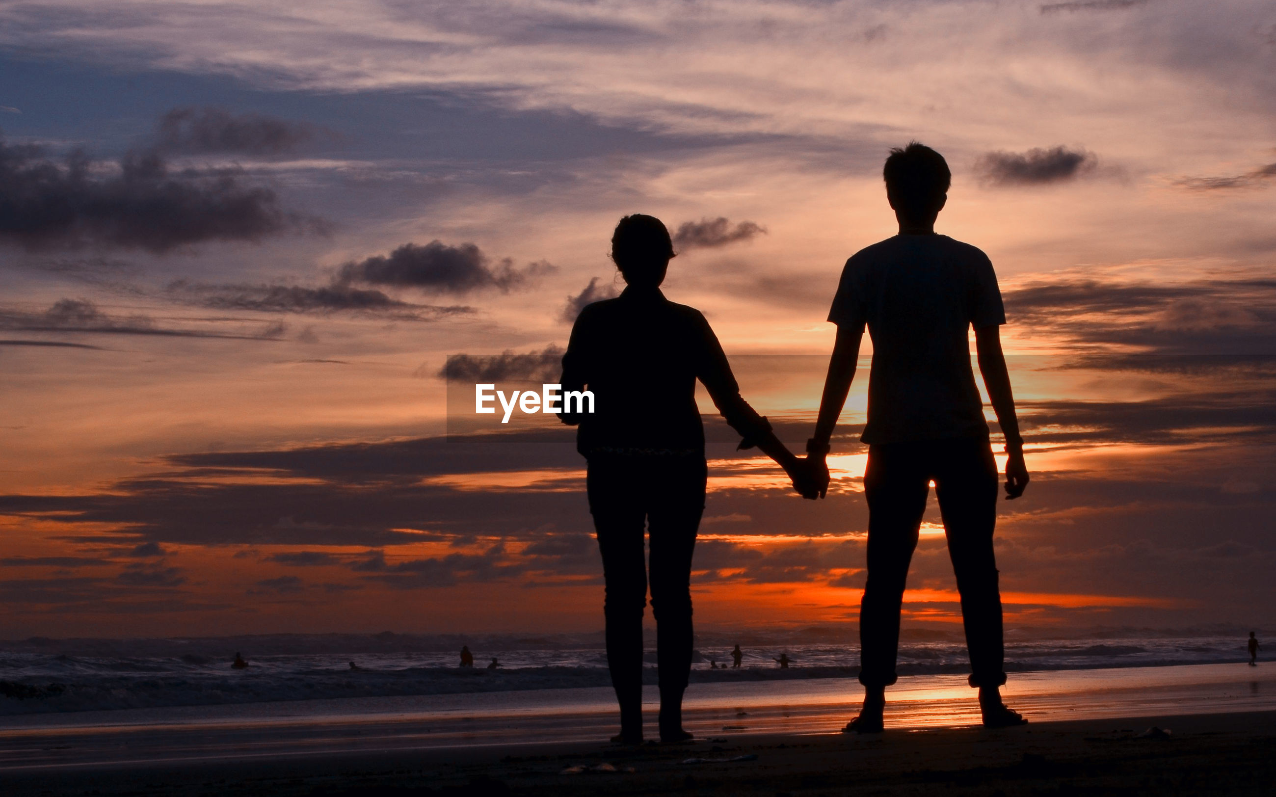 Silhouette of couple holding hands at beach against sky during sunset