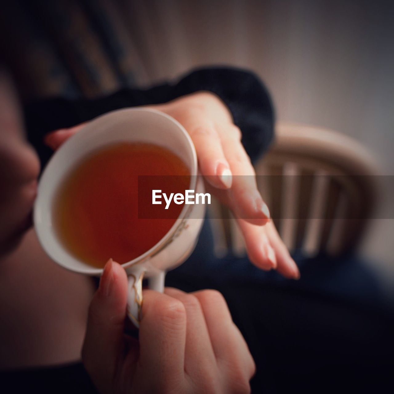 Close-Up Mid Section Of A Woman Drinking Tea
