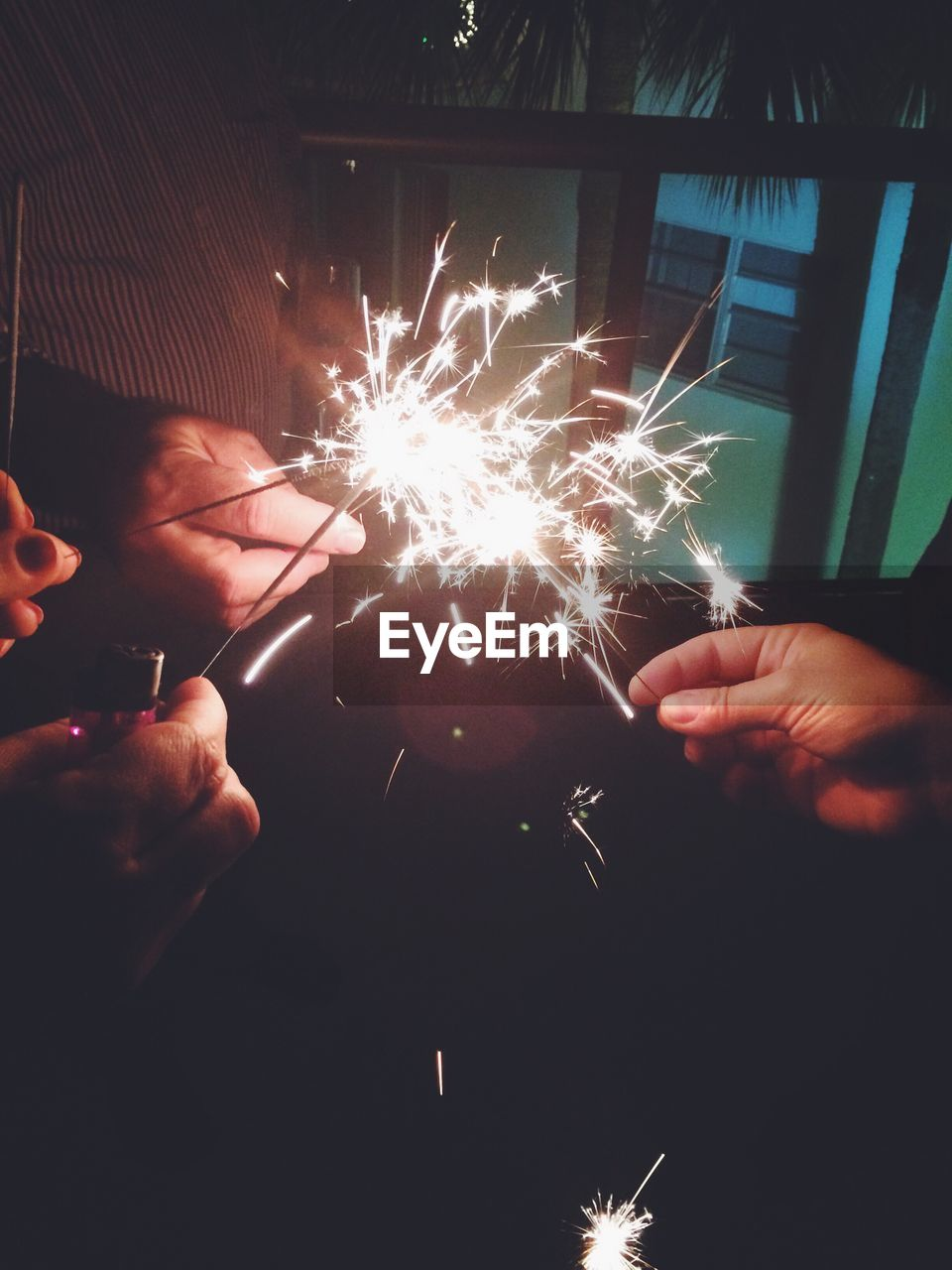Cropped Image Of Hands Holding Sparklers