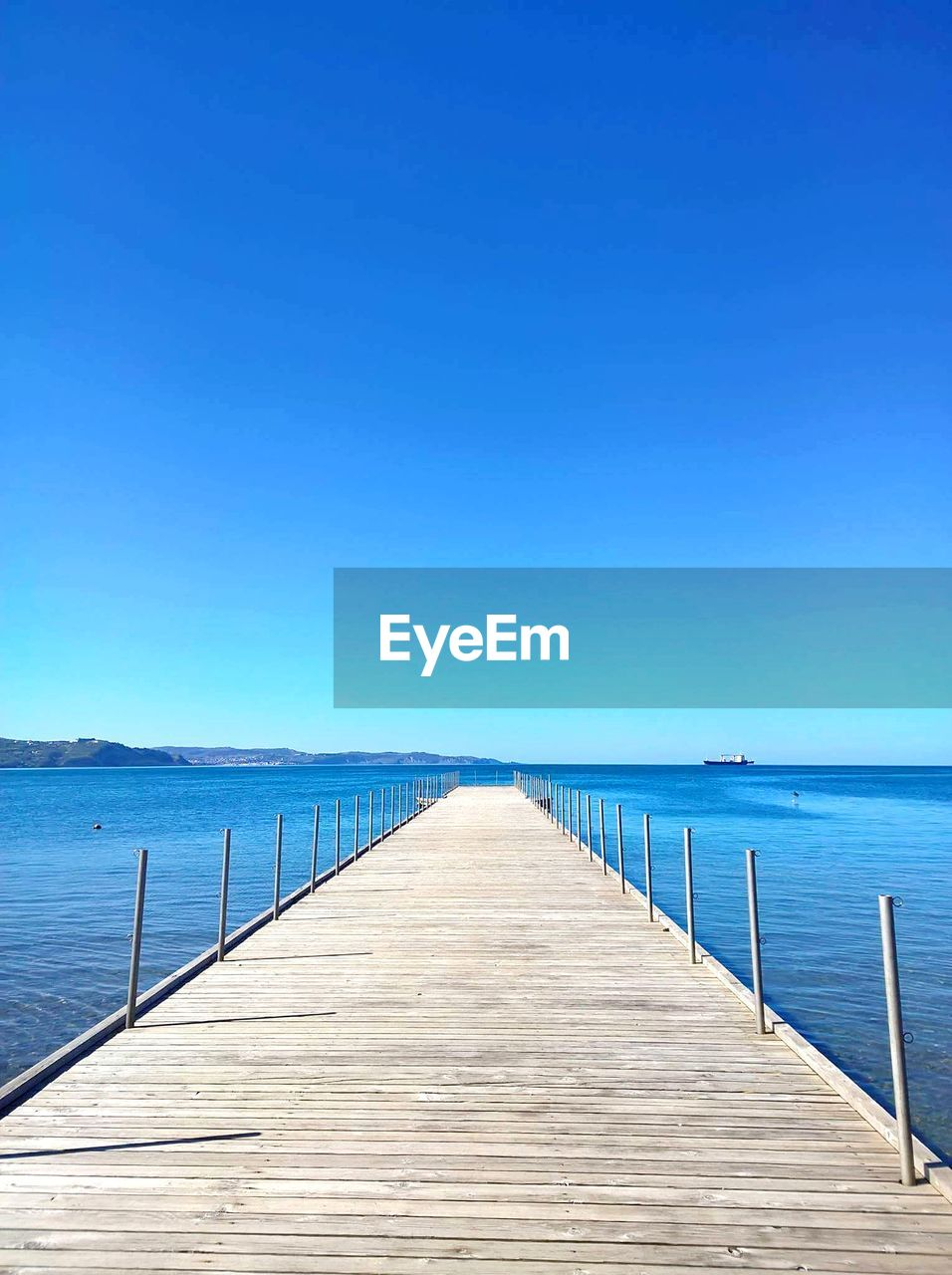 water, sea, sky, blue, clear sky, horizon over water, horizon, tranquil scene, wood - material, the way forward, tranquility, pier, beauty in nature, direction, scenics - nature, copy space, nature, no people, idyllic, diminishing perspective, outdoors, long