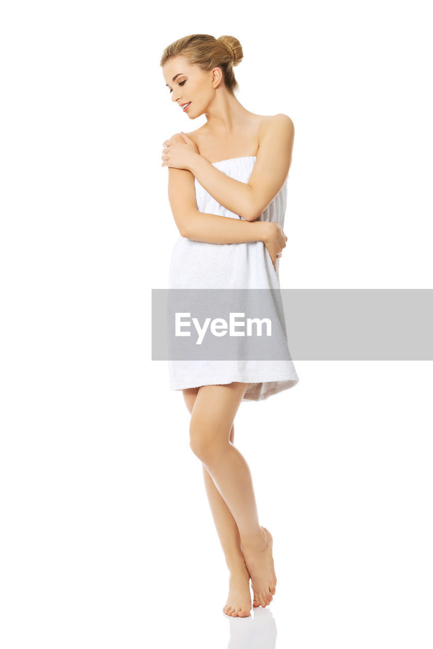 Young woman wrapped in towel standing against white background
