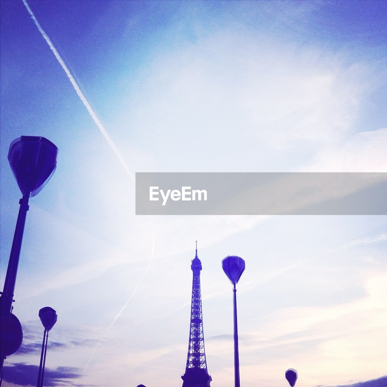 Eiffel Tower and lamp posts against sky