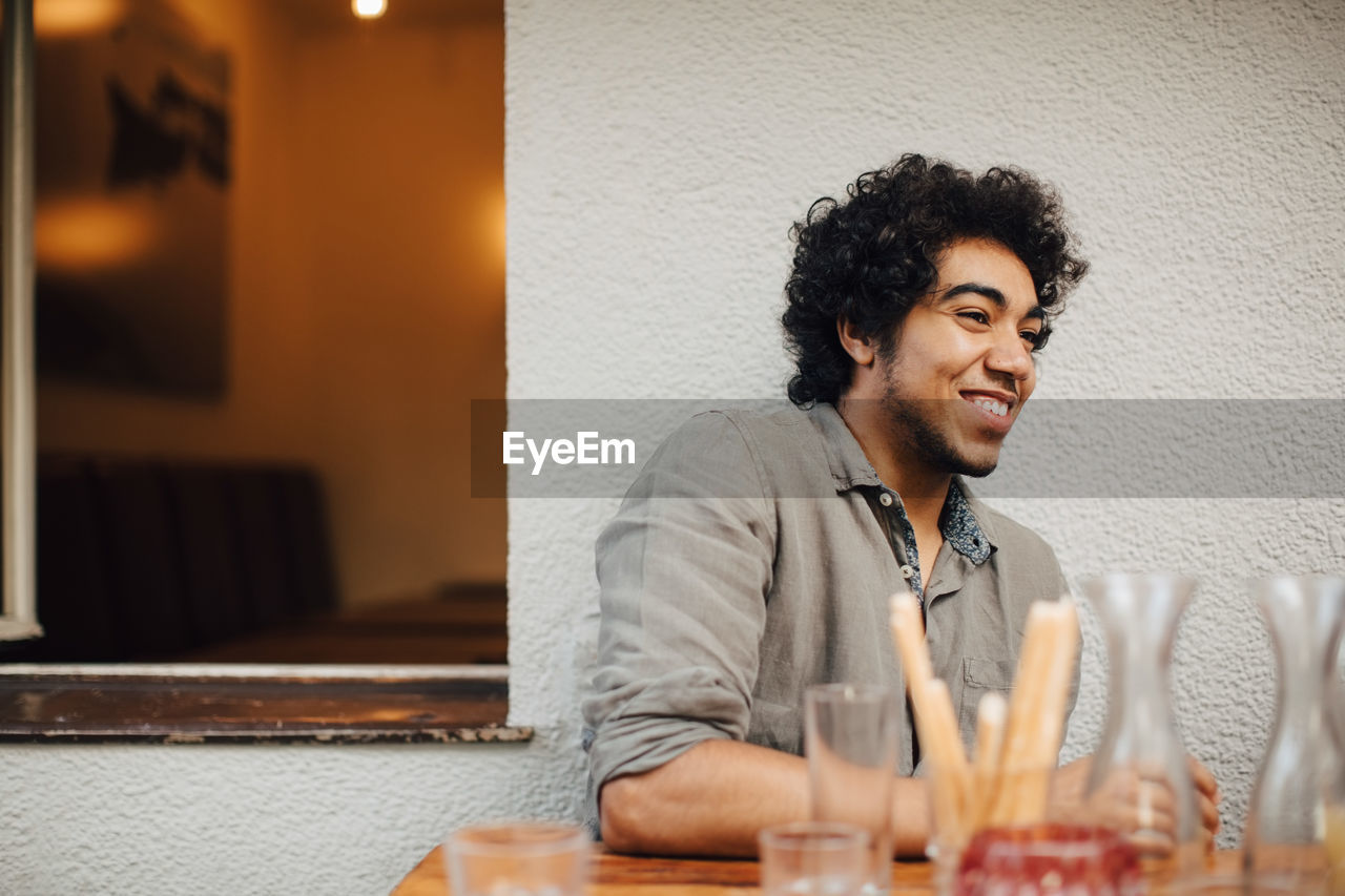 smiling, one person, indoors, portrait, young adult, real people, happiness, curly hair, lifestyles, sitting, emotion, hair, black hair, leisure activity, table, young men, casual clothing, headshot, drink, hairstyle, glass