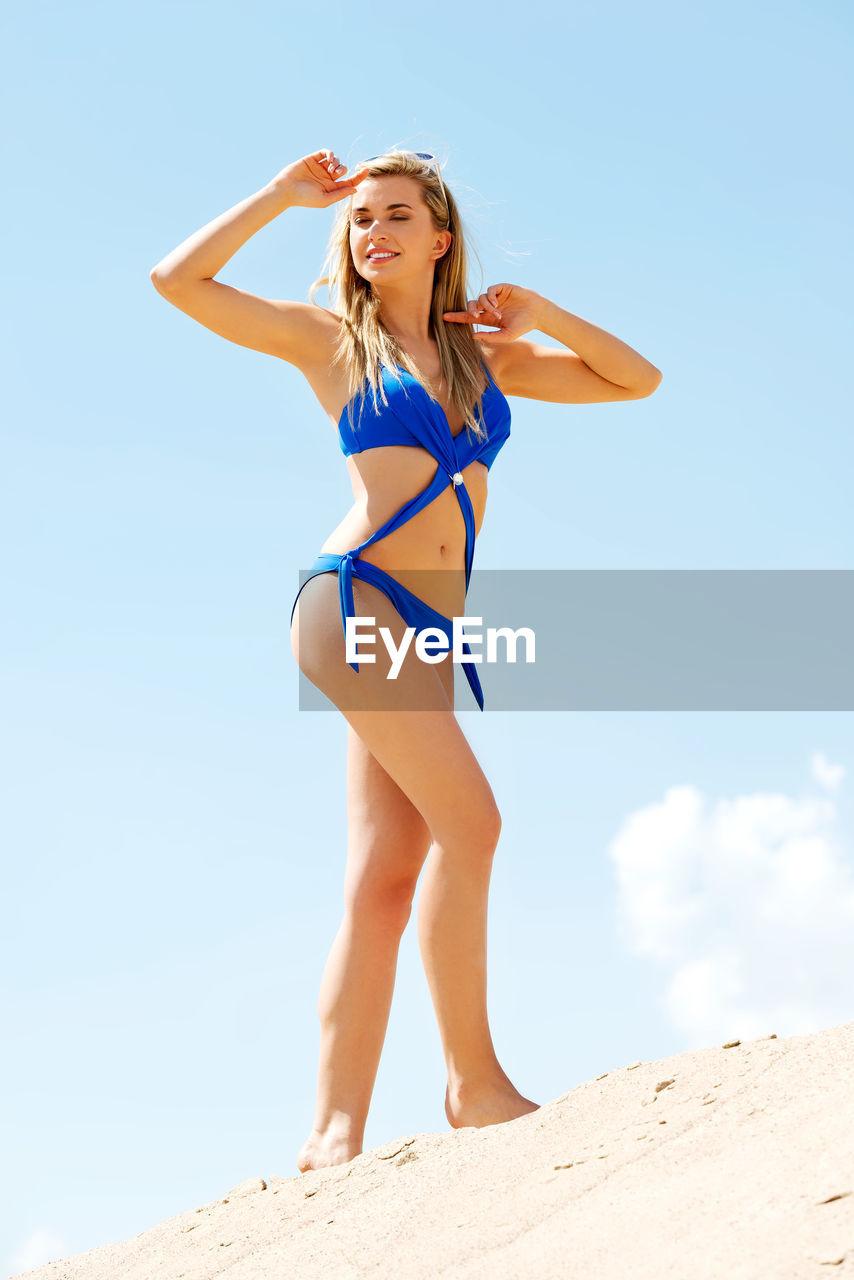 Full Length Of Woman In Bikini Standing On Beach Against Sky
