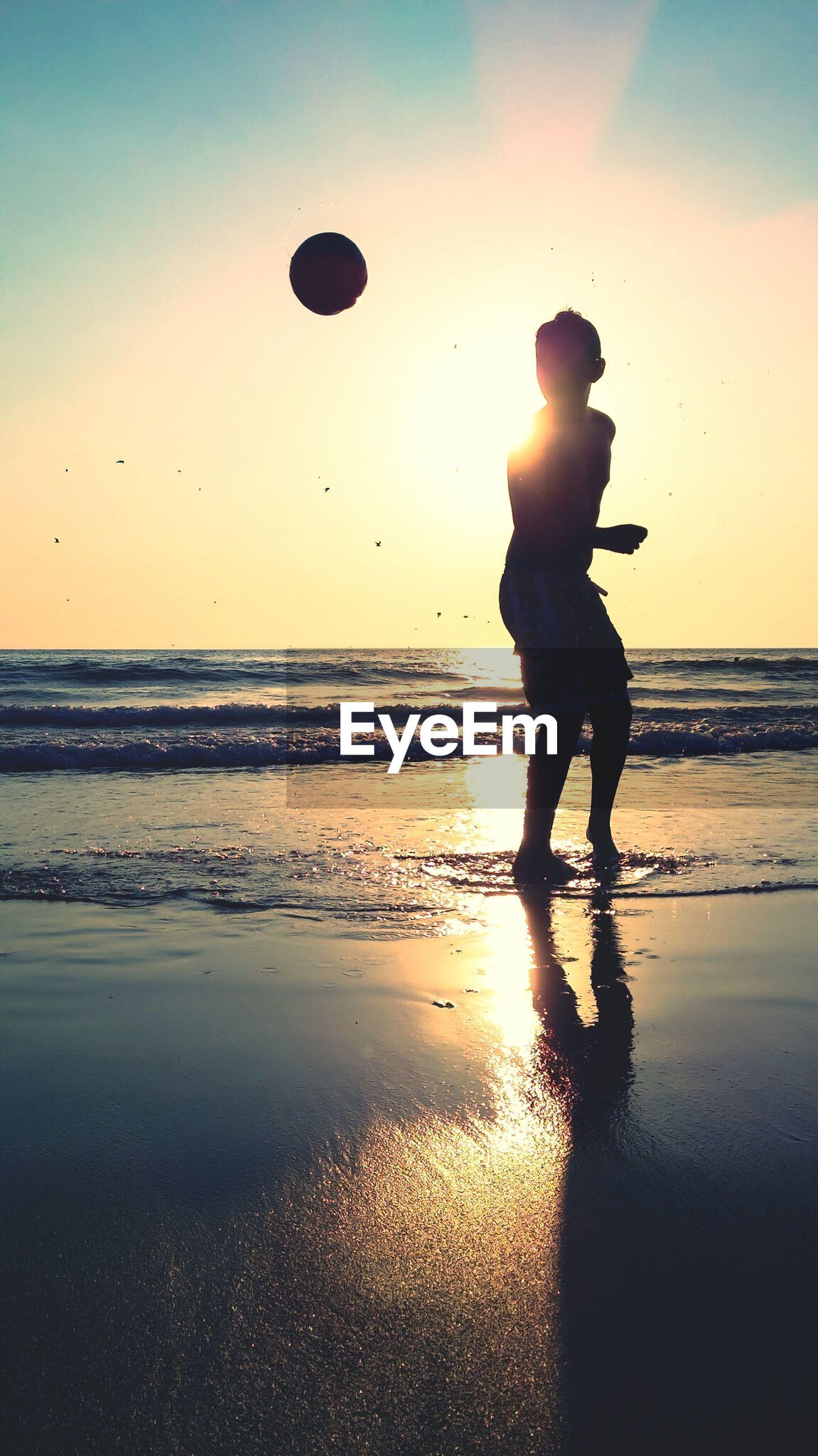 Silhouette boy playing on beach
