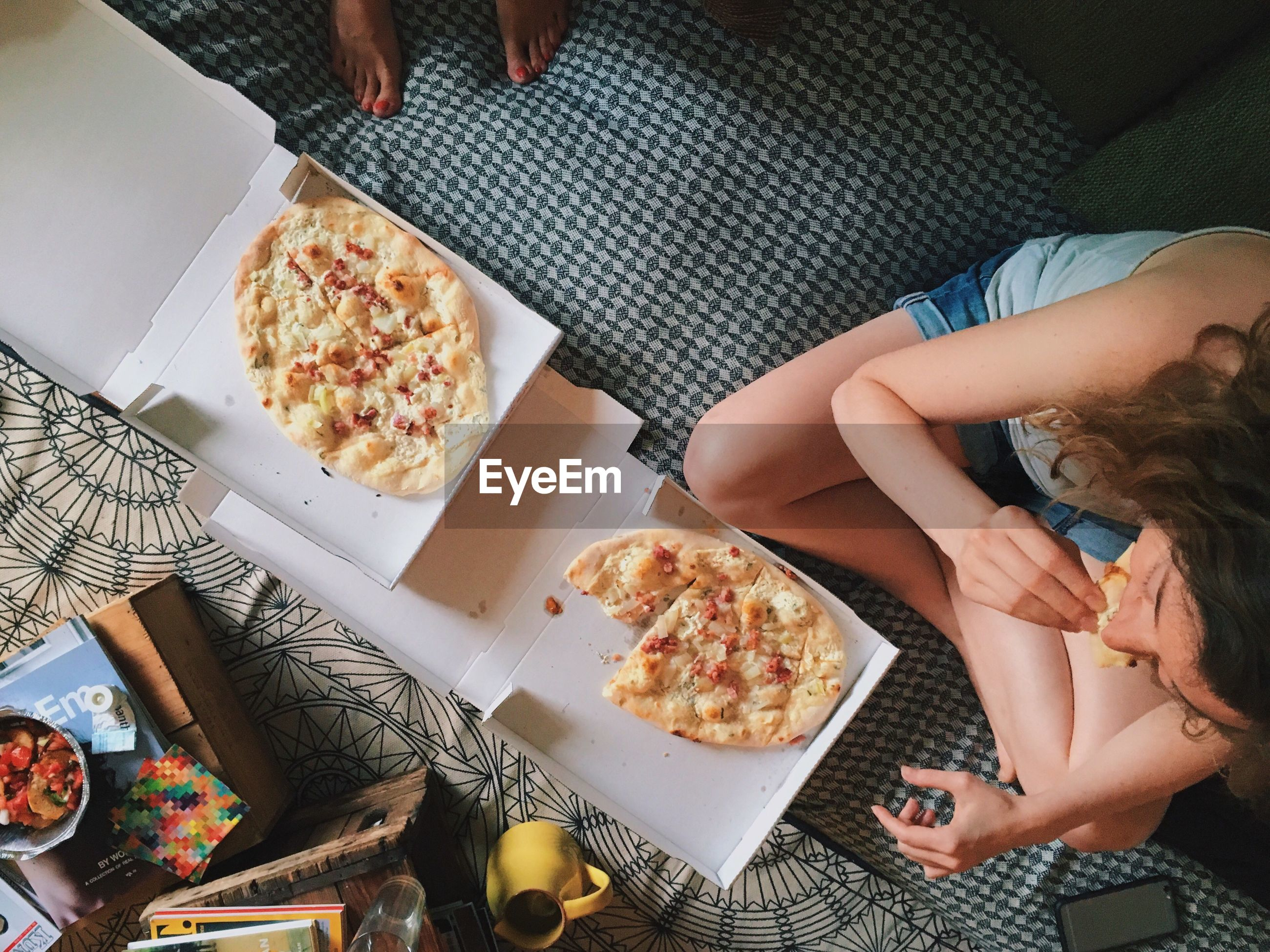 High angle view of young woman eating pizza on bed