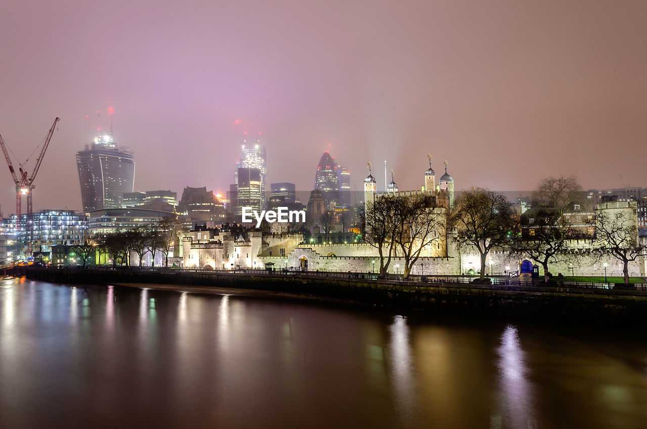 ILLUMINATED BUILDINGS BY RIVER AGAINST SKY IN CITY