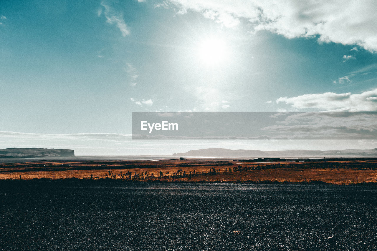 sky, scenics - nature, environment, beauty in nature, tranquil scene, landscape, sunlight, tranquility, cloud - sky, nature, land, day, sun, no people, field, non-urban scene, sunbeam, idyllic, lens flare, outdoors, bright, arid climate
