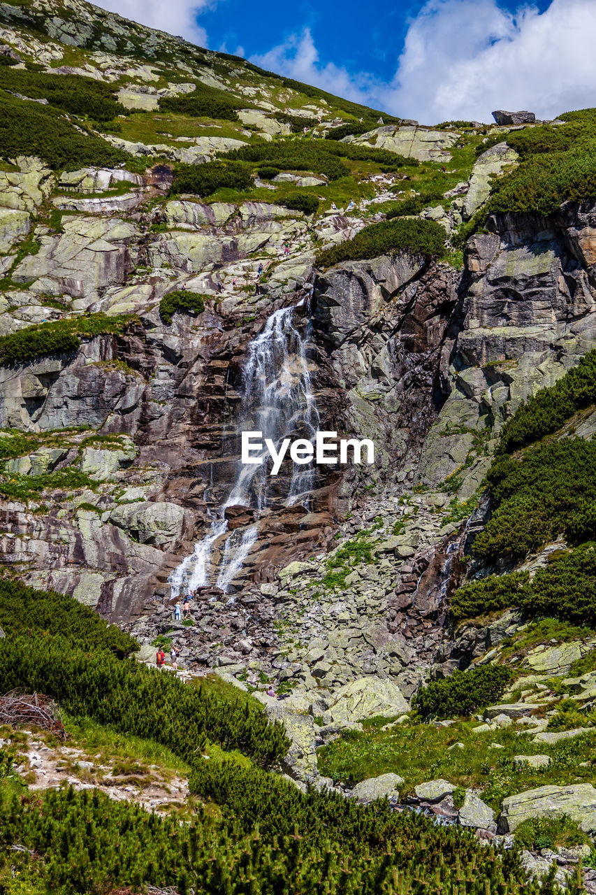 beauty in nature, scenics - nature, plant, waterfall, rock, nature, water, rock - object, land, tree, sky, non-urban scene, cloud - sky, environment, solid, no people, motion, mountain, low angle view, flowing water, outdoors, formation, power in nature, flowing