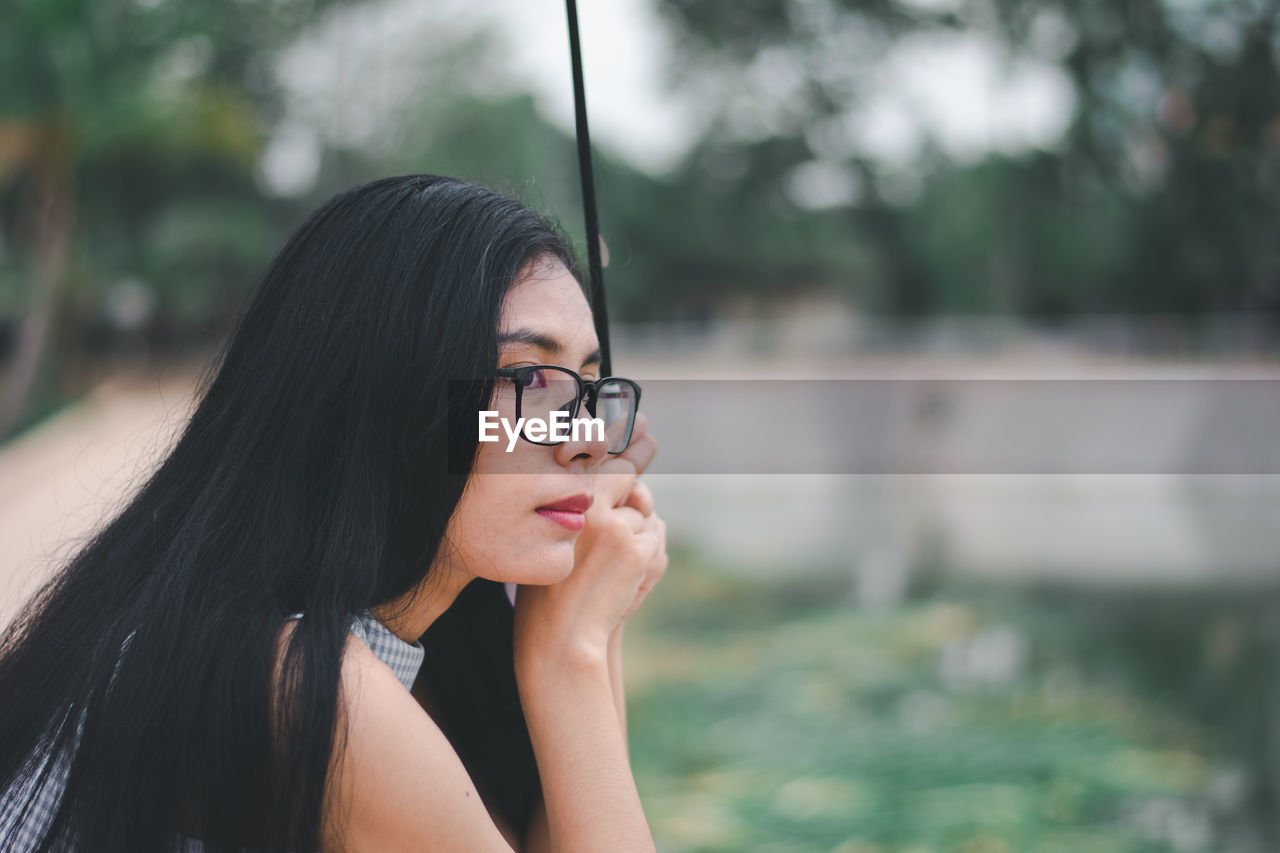 glasses, focus on foreground, one person, real people, young adult, lifestyles, headshot, portrait, leisure activity, eyeglasses, young women, black hair, hair, looking away, looking, women, beautiful woman, day, hairstyle, outdoors, contemplation, teenager
