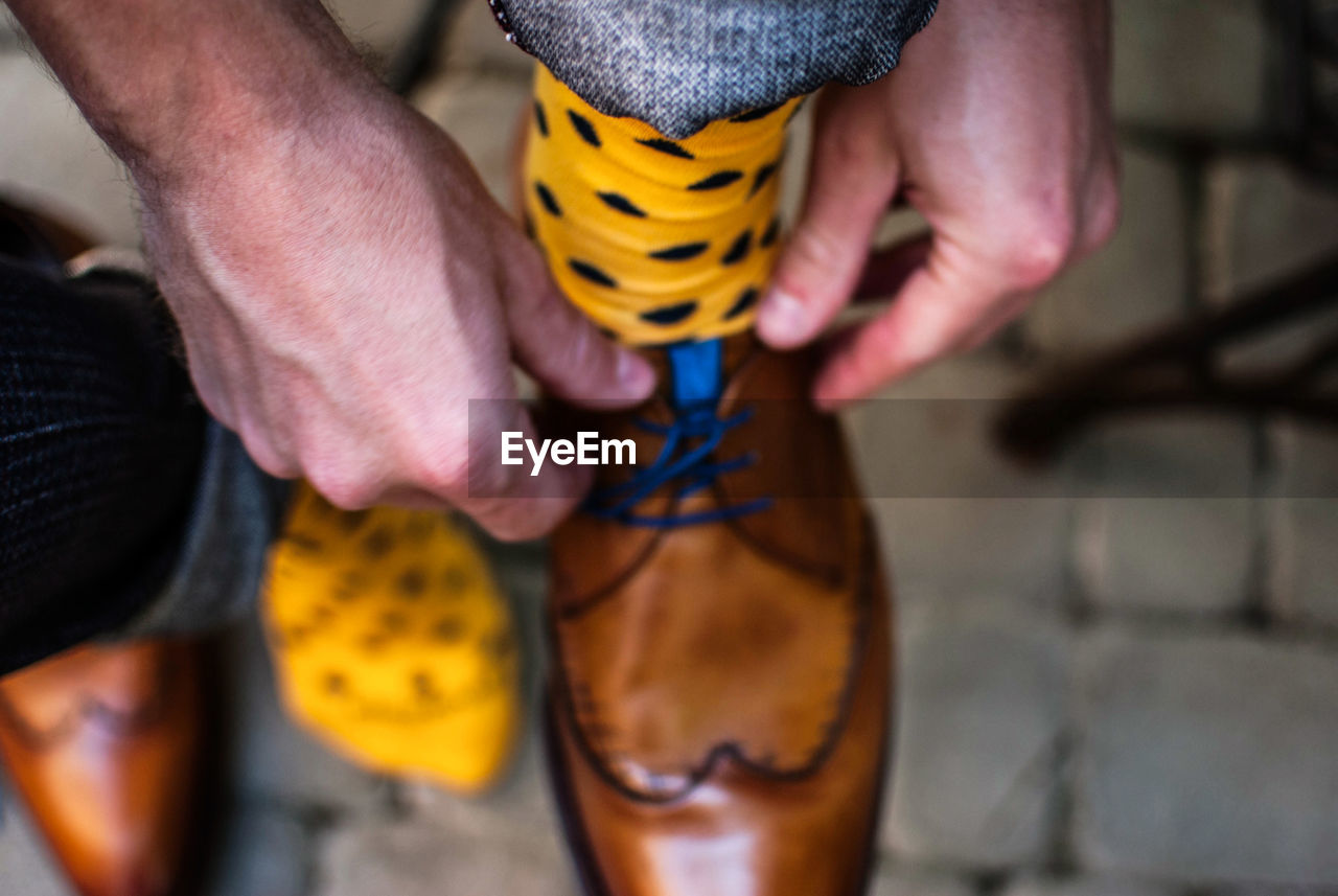 Close-up of man tying shoelaces