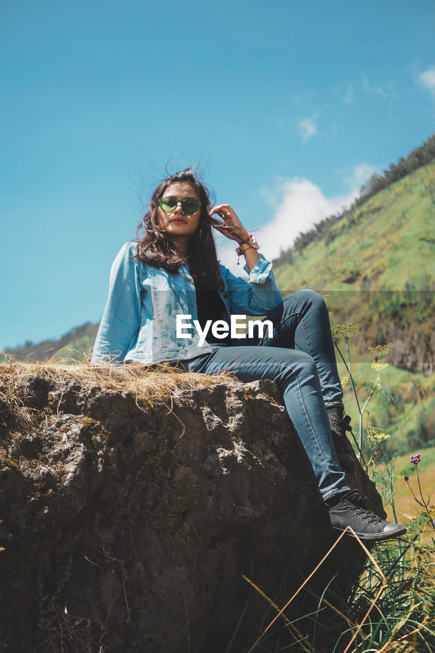 Full Length Of Young Woman Sitting On Rock