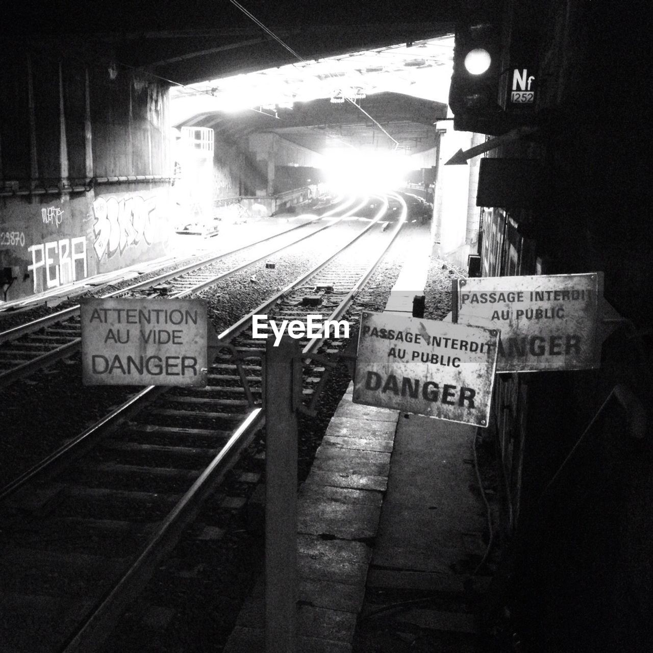 Various sign boards by railroad tracks in illuminated tunnel