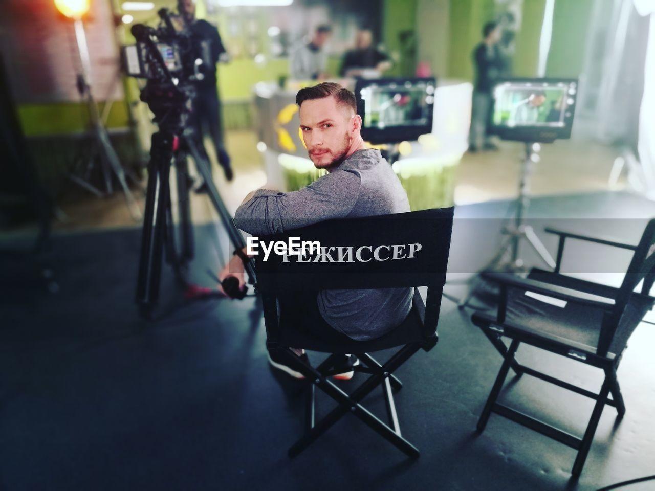 Portrait of man sitting on folding chair in studio