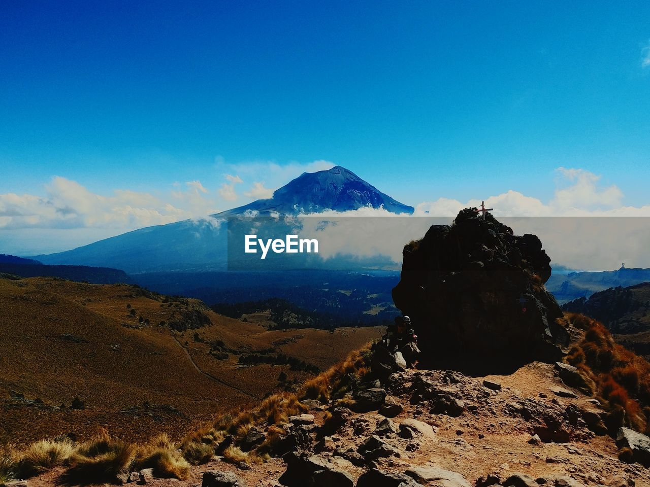 mountain, sky, scenics - nature, beauty in nature, tranquil scene, tranquility, rock, non-urban scene, landscape, solid, nature, environment, idyllic, rock - object, volcano, cloud - sky, land, no people, blue, mountain peak, mountain range, outdoors, snowcapped mountain, volcanic crater