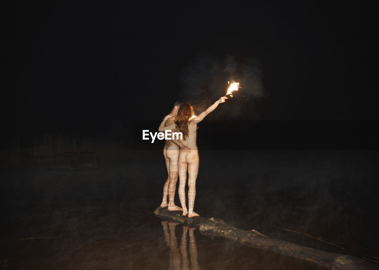 Rear view of naked couple holding flaming torch while standing on driftwood at lakeshore