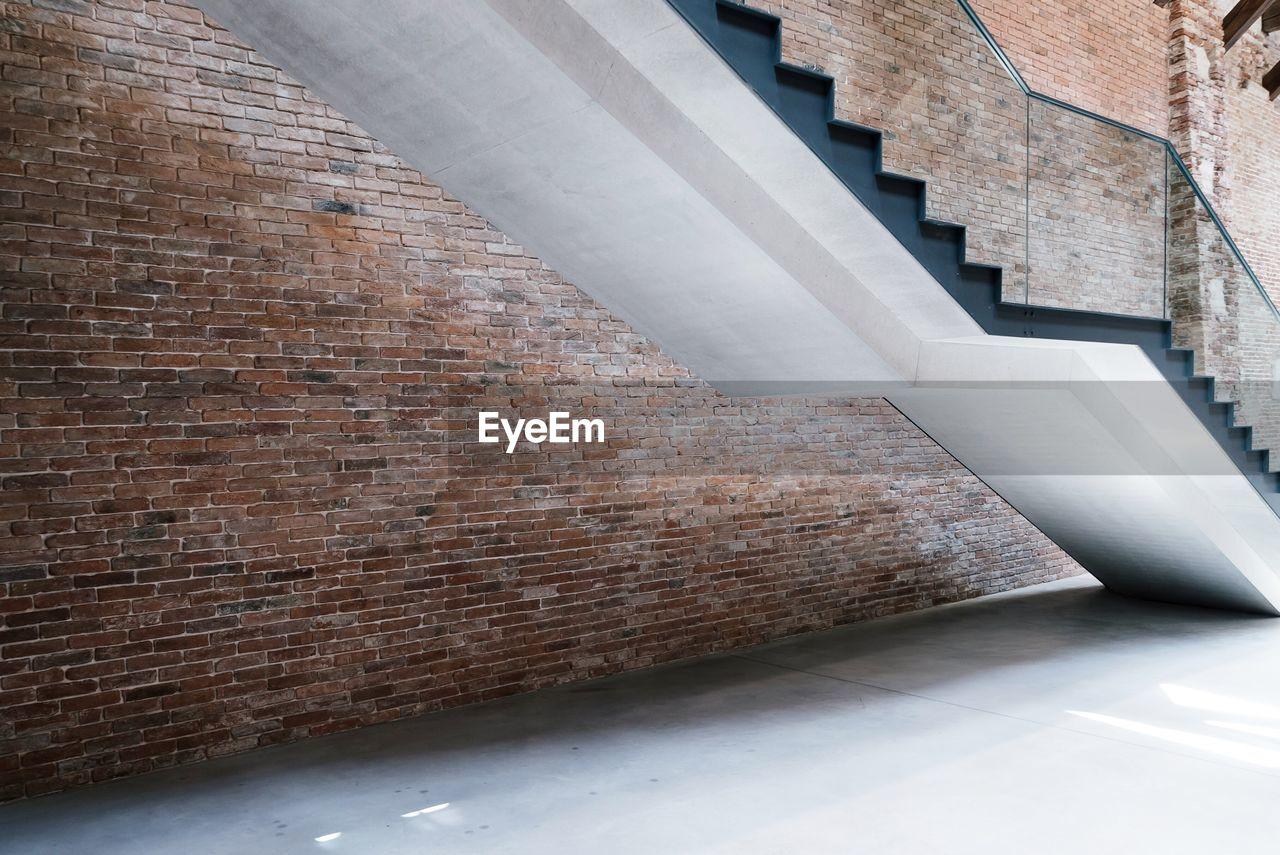 Steps by brick wall