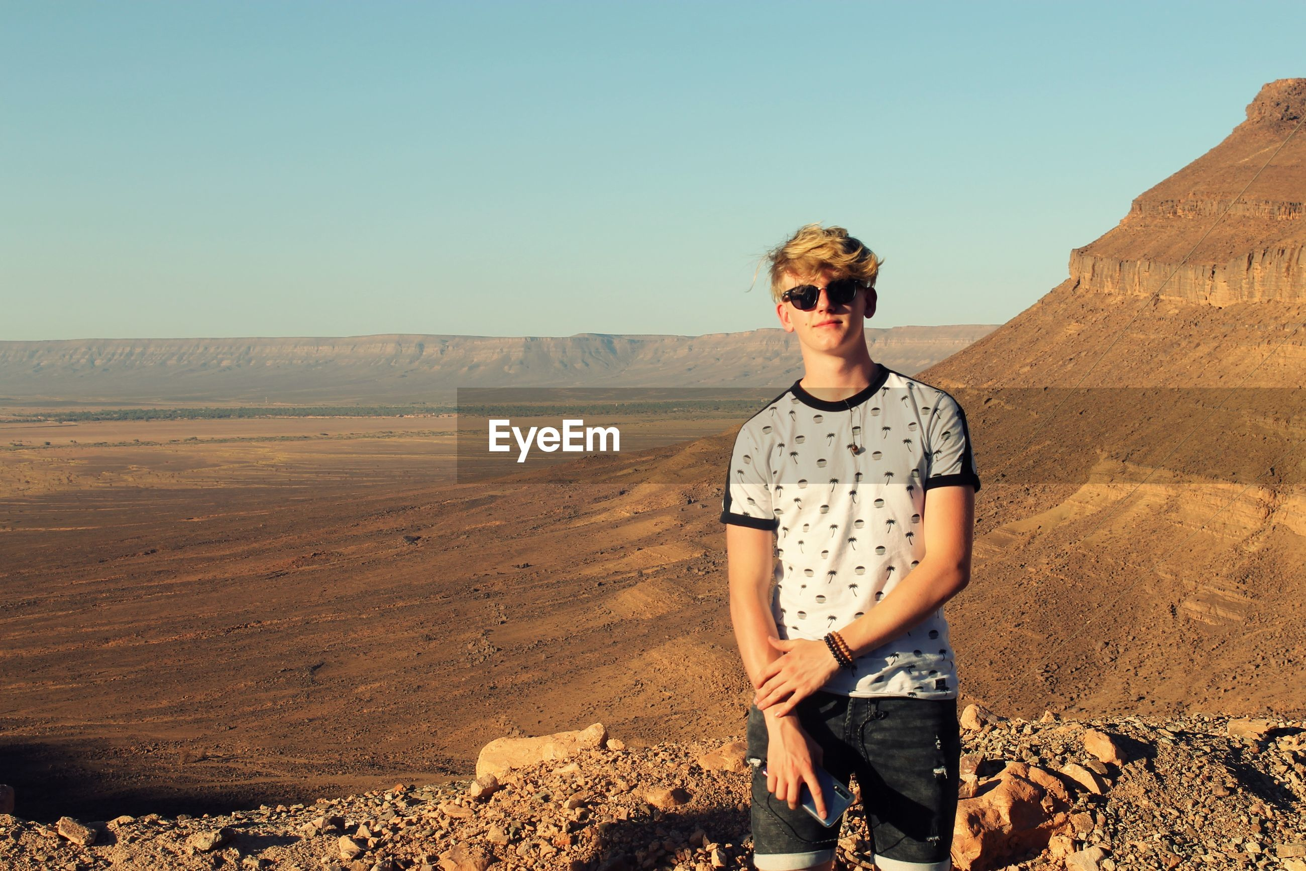 Boy wearing sunglasses at desert against clear sky