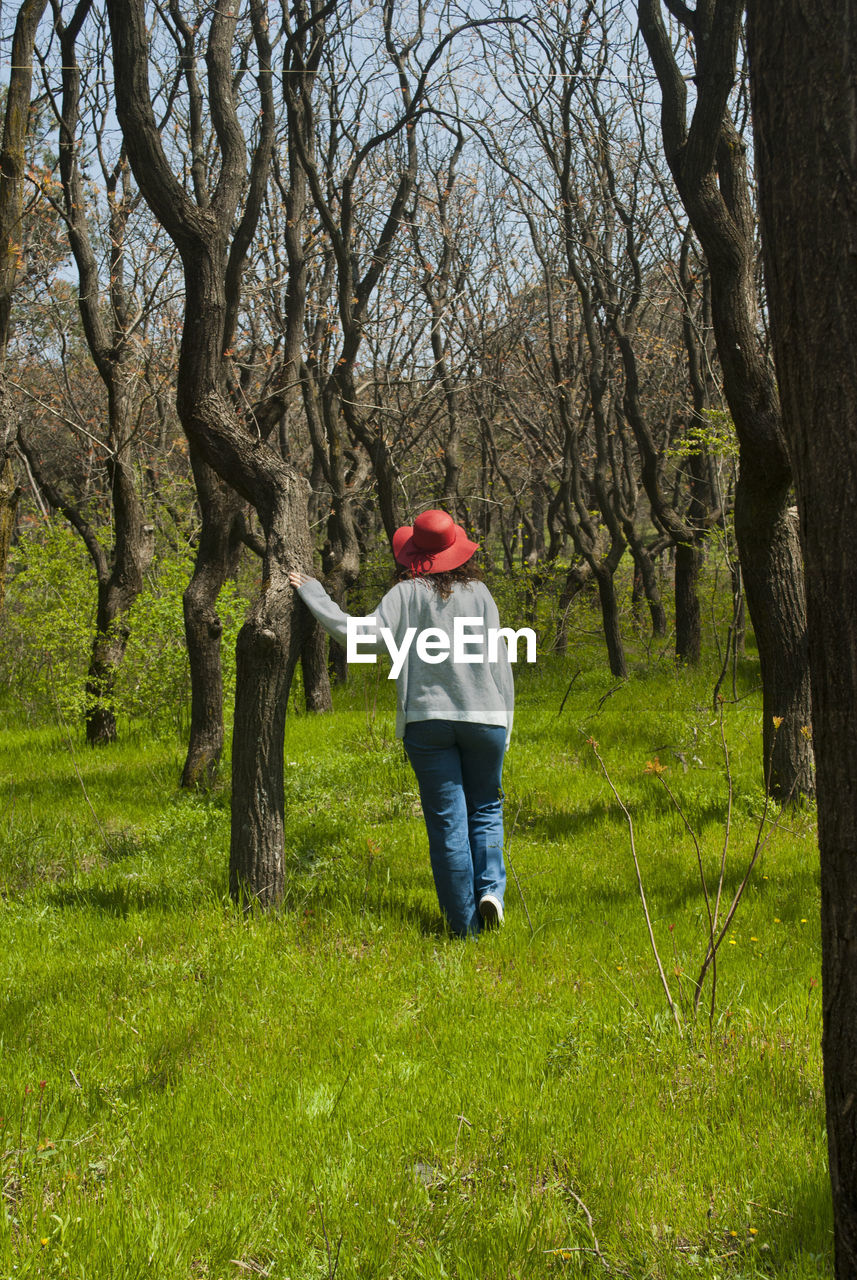 Rear view of woman walking on field against bare trees