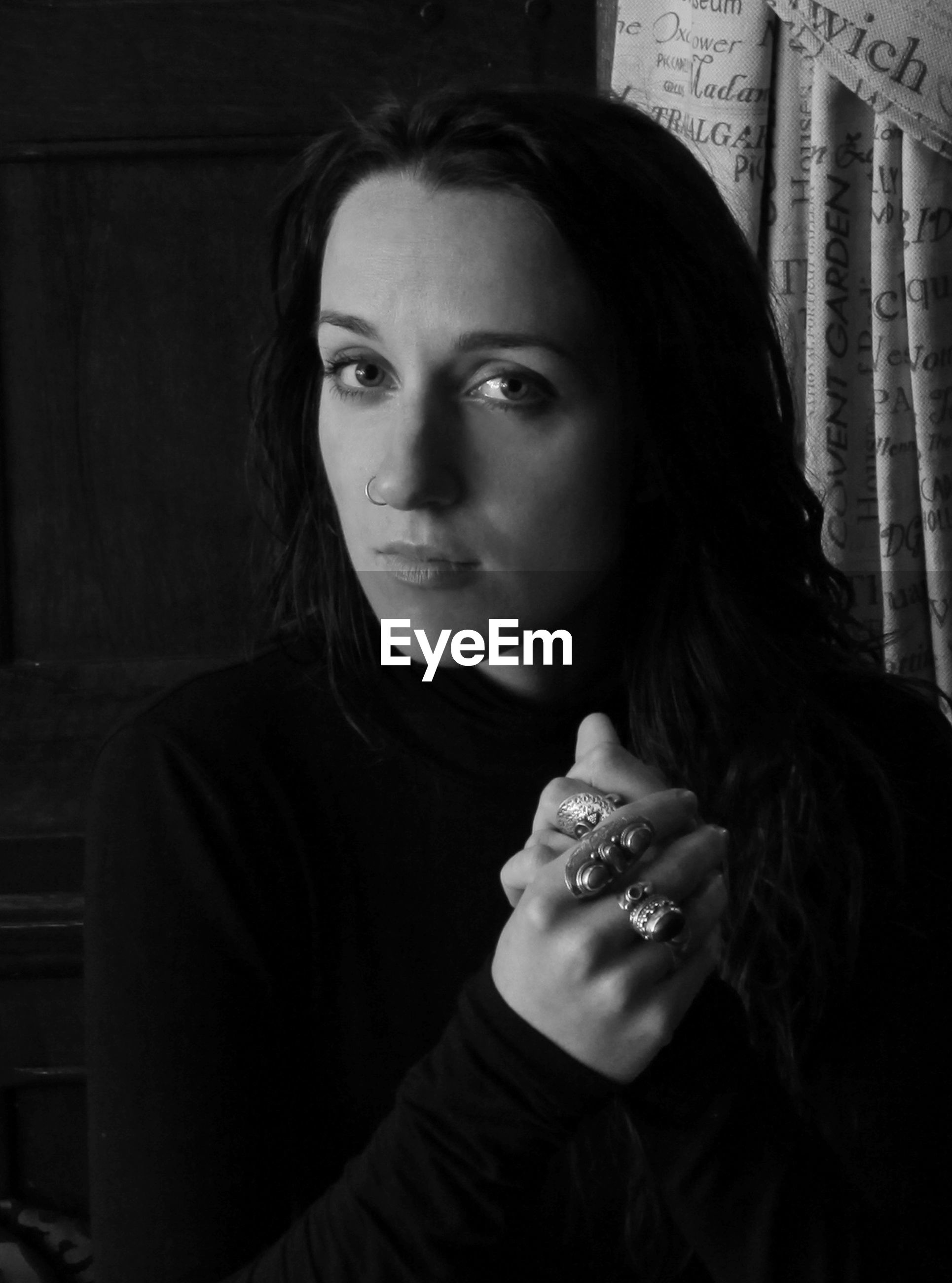 Portrait of woman wearing various rings standing at home