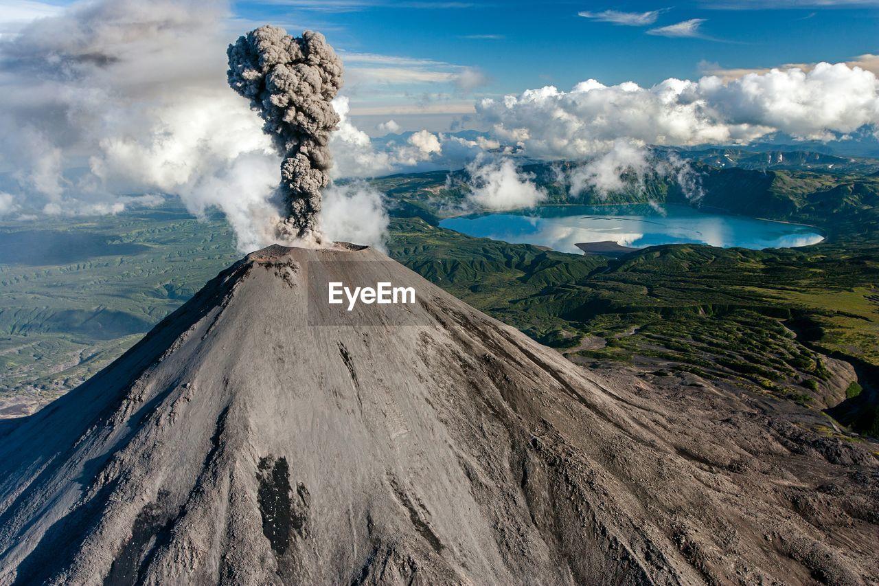View of karymsky volcano erupting against sky