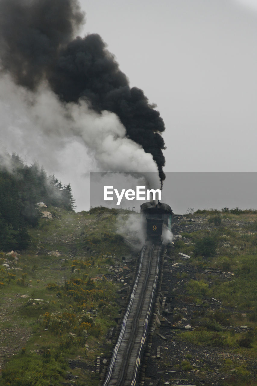 smoke - physical structure, rail transportation, train, transportation, mode of transportation, train - vehicle, pollution, steam train, sky, public transportation, plant, air pollution, nature, emitting, railroad track, track, environmental issues, tree, smoke, day, no people, outdoors