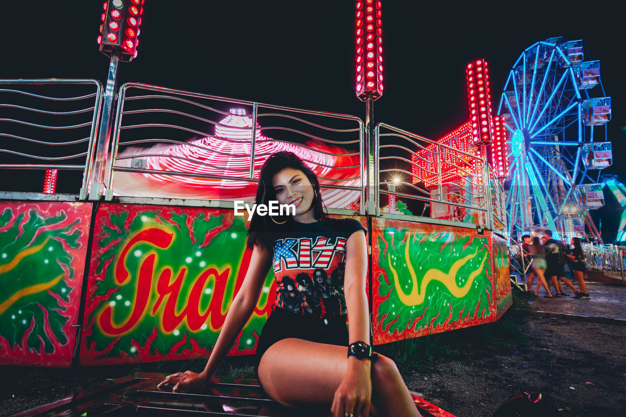 amusement park, amusement park ride, arts culture and entertainment, leisure activity, real people, lifestyles, night, illuminated, casual clothing, front view, one person, portrait, women, looking at camera, young adult, emotion, enjoyment, ferris wheel, young women, outdoors, positive emotion