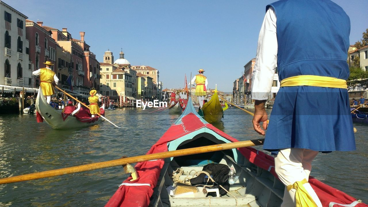 Midsection Of Man In Gondola On Grand Canal Against Sky