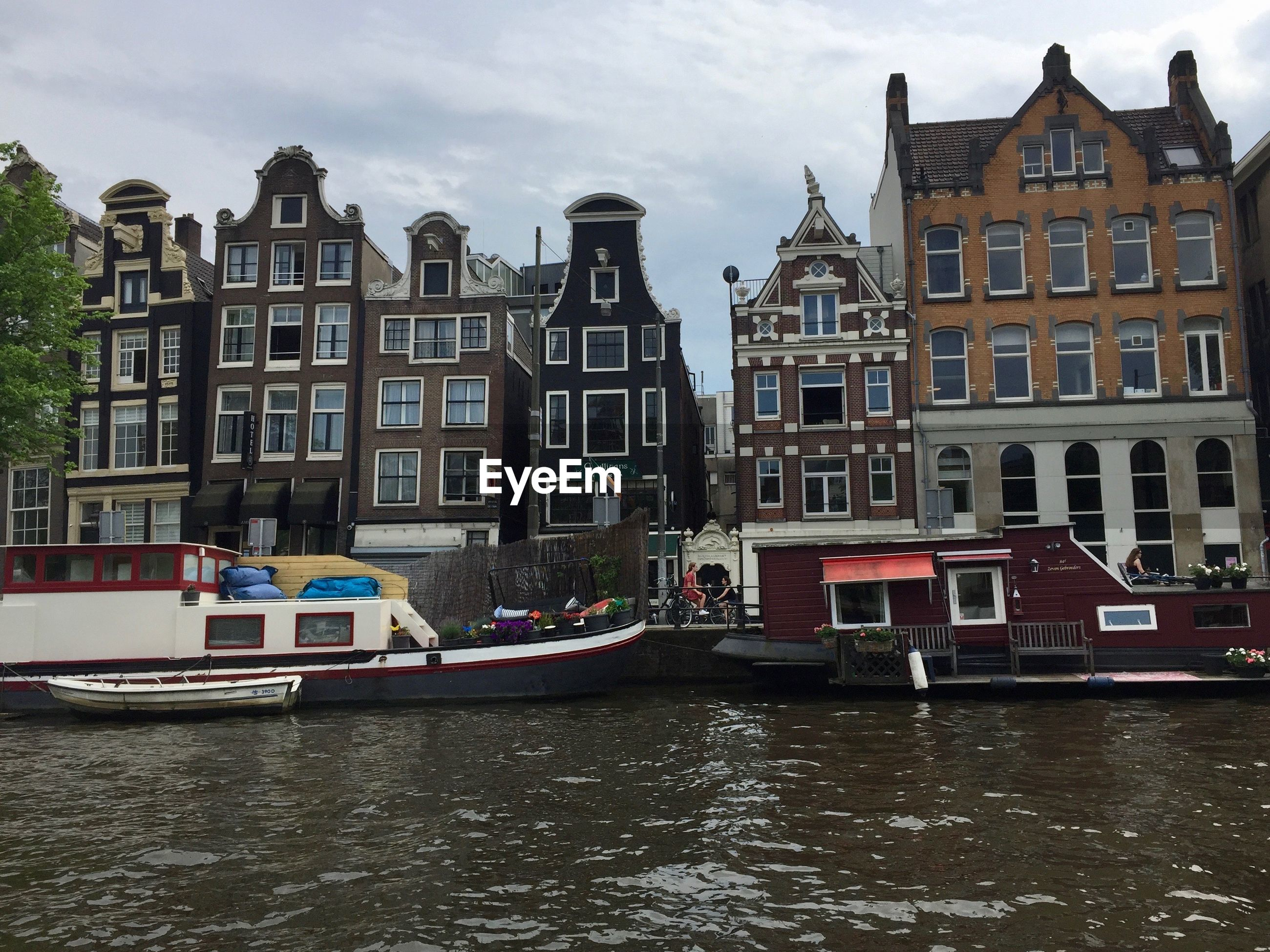 BOATS IN CANAL BY BUILDINGS AGAINST SKY