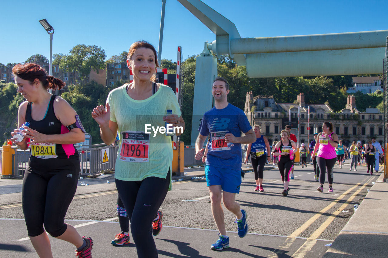 real people, lifestyles, outdoors, day, leisure activity, running, casual clothing, women, sports race, togetherness, sunlight, smiling, happiness, young women, sports clothing, men, young adult, marathon