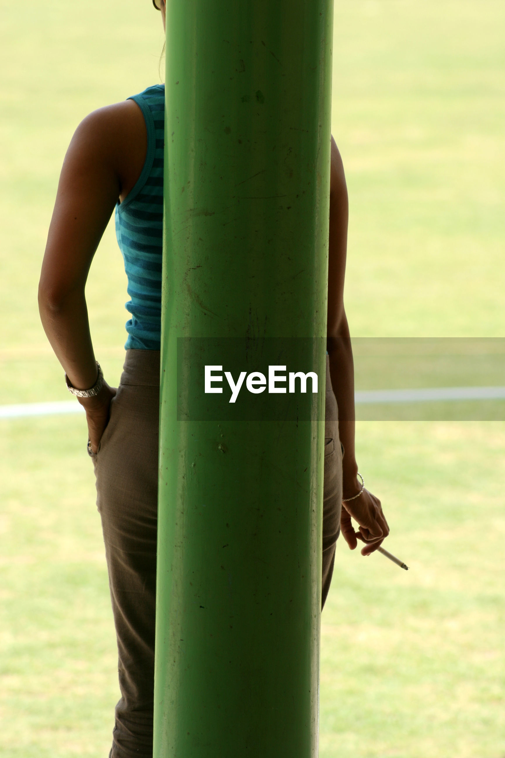 Rear view of woman with cigarette standing by green pole