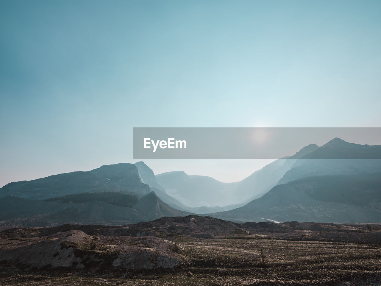 mountain, sky, environment, landscape, nature, beauty in nature, scenery, mountain peak, mountain range, clear sky, travel, sun, sunlight, outdoors, bright, lens flare, no people, wilderness, range, height, high