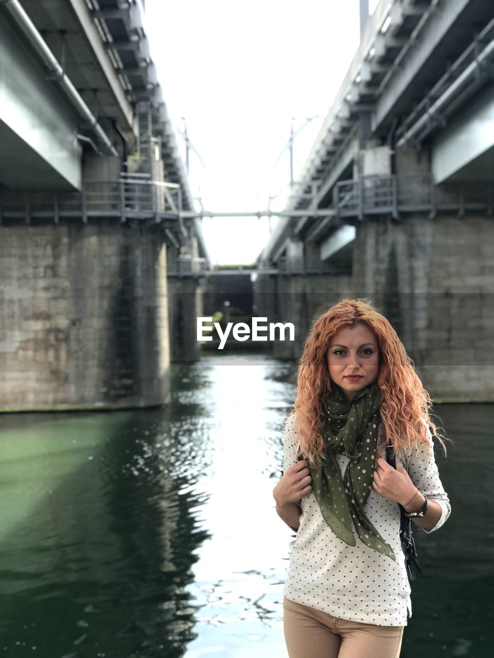 one person, water, young women, young adult, built structure, architecture, hairstyle, long hair, looking at camera, leisure activity, hair, real people, lifestyles, standing, women, portrait, clothing, front view, bridge - man made structure, beautiful woman, outdoors, canal, warm clothing