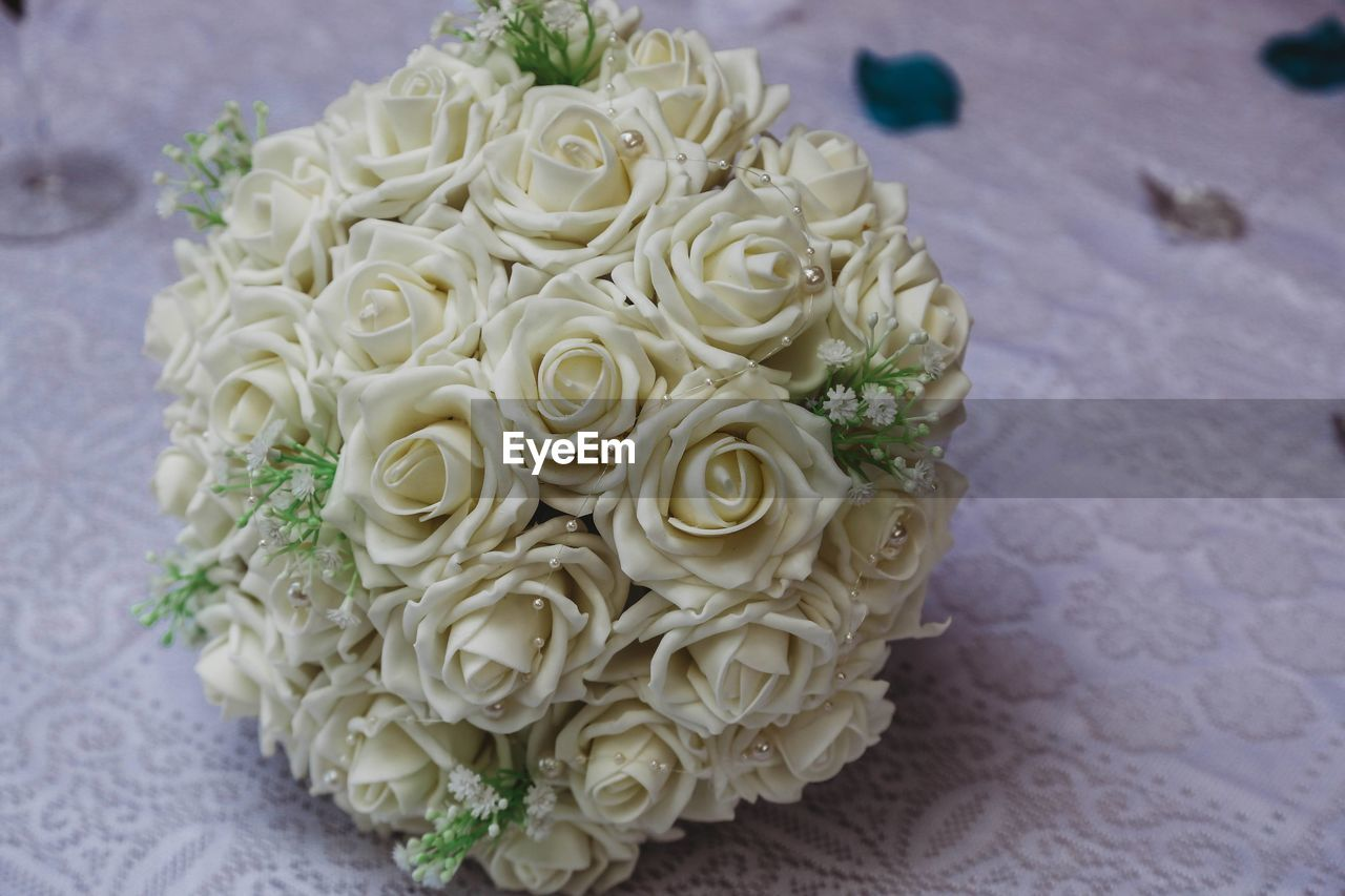 HIGH ANGLE VIEW OF WHITE ROSE BOUQUET ON TABLE