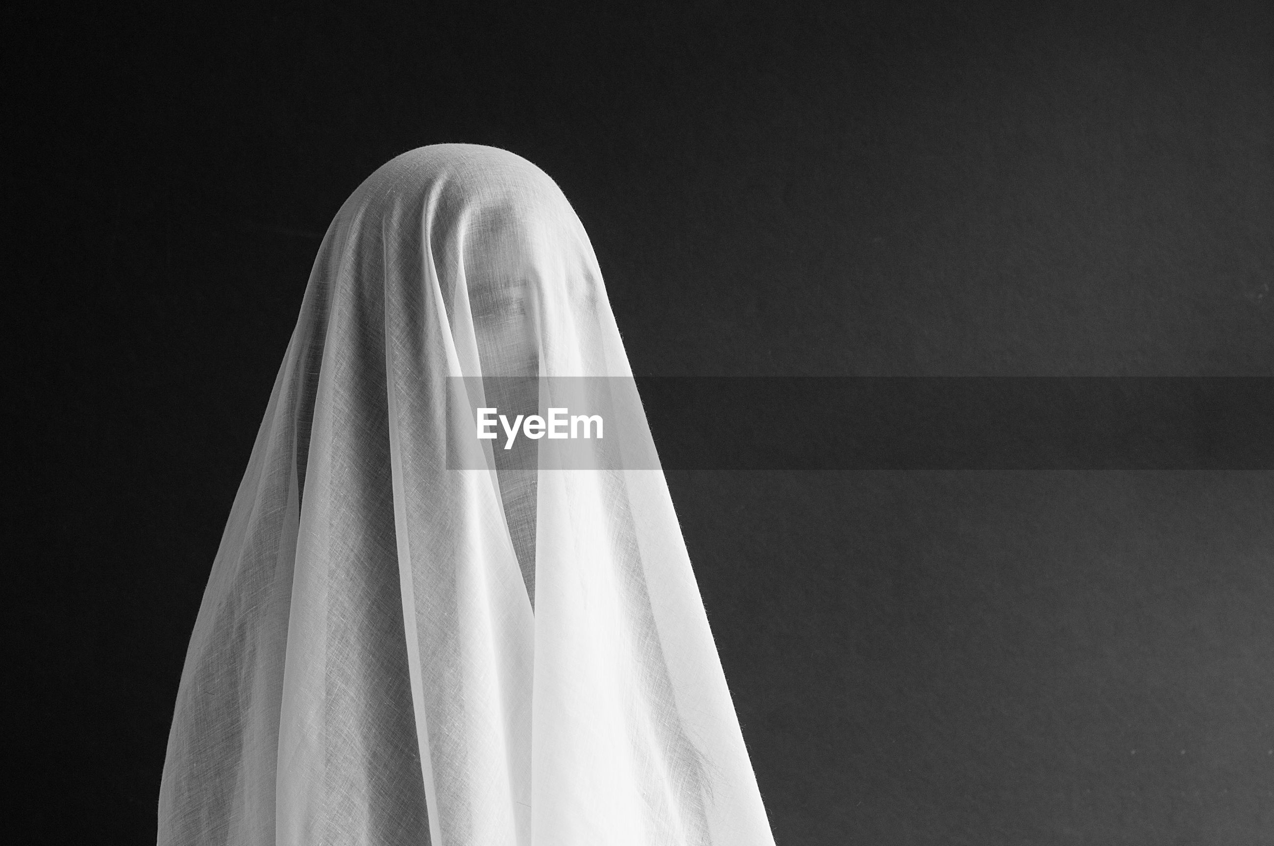 Close-up of woman in veil against gray background