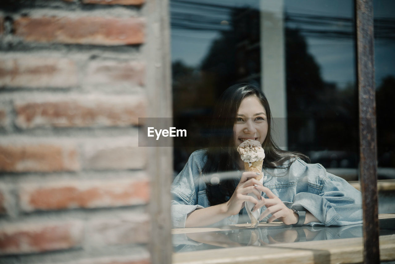 Smiling young woman holding ice cream in store
